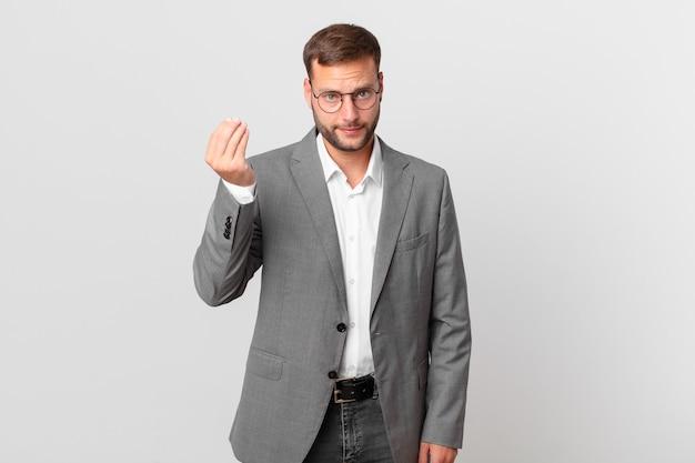 잘생긴 사업가가 돈을 지불하라고 말하거나 몸짓을 하고 있다