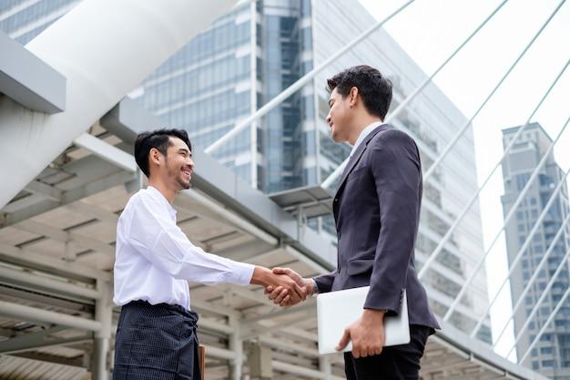 都市のasean経済コミュニティの握手協定とのハンサムなビジネスマンのパートナーシップ