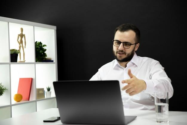 Handsome businessman pointing to monitor, talks online by webcam, remote work