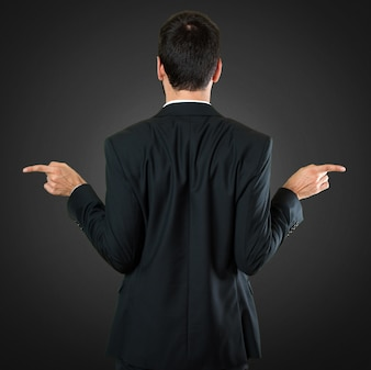 Handsome businessman pointing to the laterals having doubts on black background