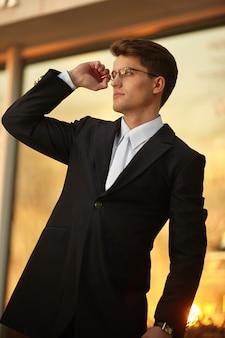 안경과 검은 양복을 입고 포즈를 취하는 잘생긴 사업가는 손에 시계를 착용합니다.