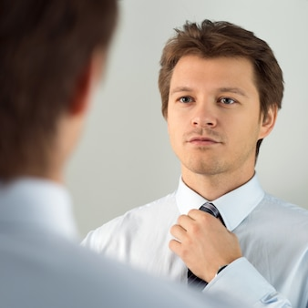 Handsome businessman preparing to official event, straighten tie