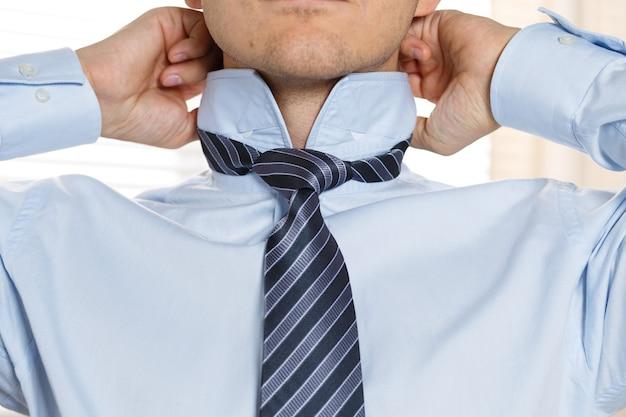 公式イベントの準備をしているハンサムなビジネスマン、ネクタイをまっすぐにします。新しい就職の面接、自信への自己動機付け、ファッショナブルなネクタイの結び目を試す、サービスのコンセプトを調整する