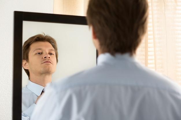 公式イベントの準備をしているハンサムなビジネスマン、ネクタイをまっすぐにします。新しい就職の面接、自信への自己動機付け、ファッショナブルなネクタイの結び目、仕立てサービス、またはデートのコンセプトを試す