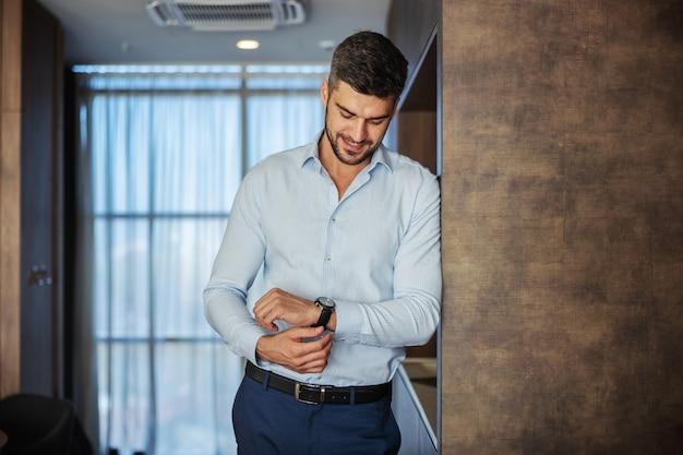 Handsome businessman putting wristwatch on hand