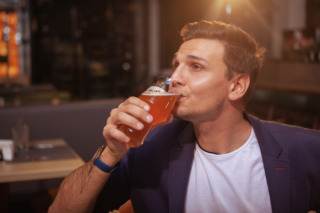 Handsome businessman relaxing at beer pub after working day