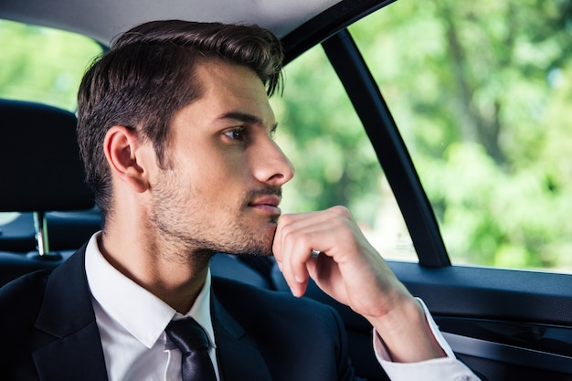 Handsome businessman riding in car