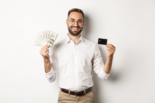 Handsome businessman showing credit card and money dollars, smiling pleased, standing over white background.