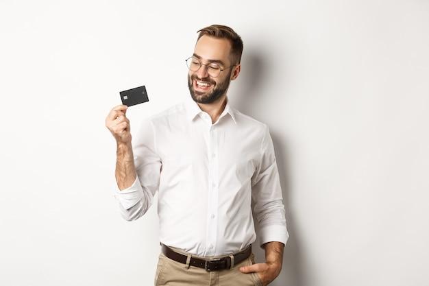 그의 신용 카드를 보여주는 잘 생긴 사업가 만족, 서 찾고