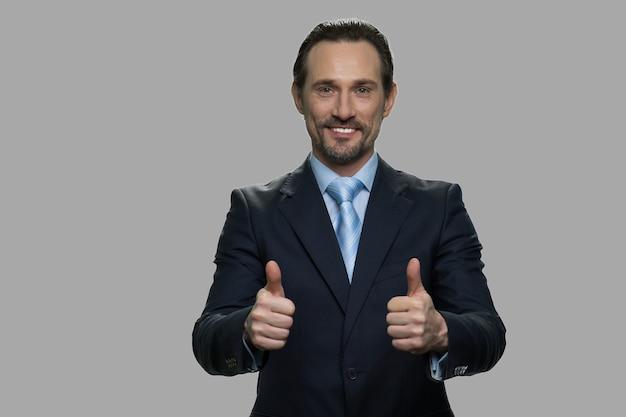 2つの親指を上に示しているハンサムなビジネスマン。灰色の背景にカメラを見ている魅力的なceo。大成功のコンセプト。