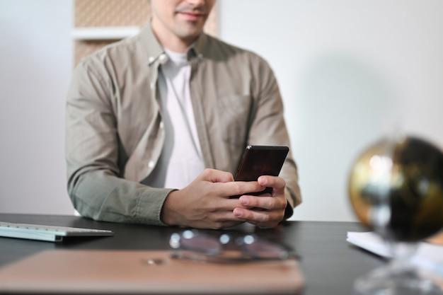 Красивый бизнесмен сидит на своем рабочем месте и с помощью смартфона.