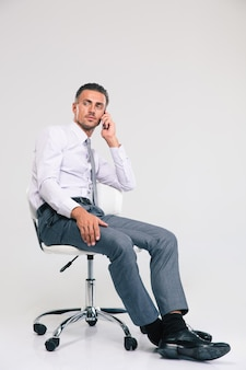 Handsome businessman sitting on office chair and talking on the phone isolated