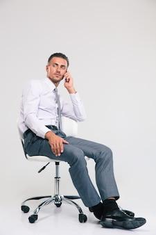 Красивый бизнесмен сидит на офисном стуле и разговаривает по телефону изолированы