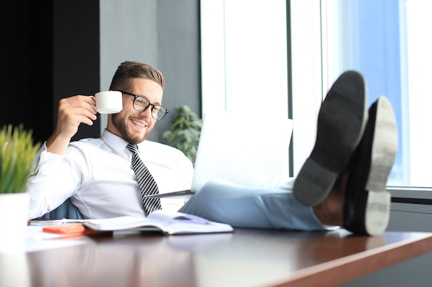 Handsome businessman sitting with legs on table and drinking coffee in office.