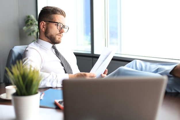 Handsome businessman sitting with legs on table and examing documents in office.