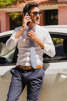 Красивый бизнесмен, стоя возле своего автомобиля, разговаривает по мобильному телефону