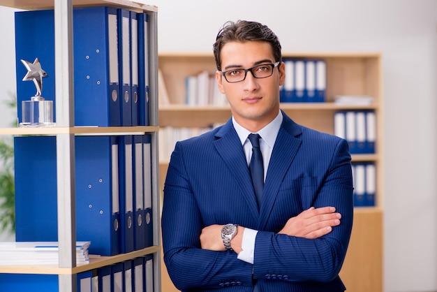 Handsome businessman standing next to shelf