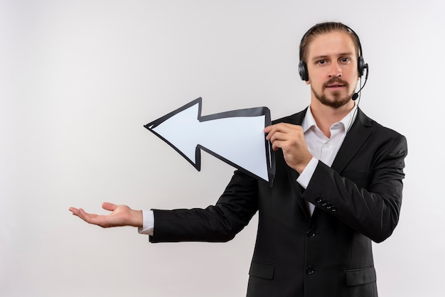 Handsome businessman in suit and headphones with a microphone holding white arrow looking at camera presenting with arm copy space standing over white background