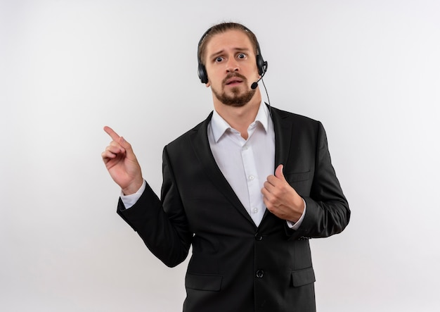 Handsome businessman in suit and headphones with a microphone looking at camera confused pointing with fingers to the side standing over white background