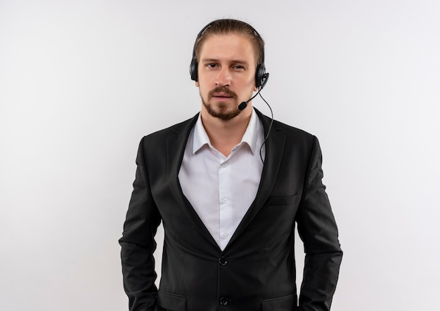 Handsome businessman in suit and headphones with a microphone looking at camera with confident expression standing over white background