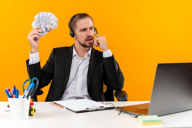 Handsome businessman in suit and headphones with a microphone showing cash looking aside thinking sitting at the table in offise over orange background