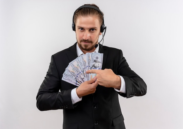 Handsome businessman in suit and headphones with a microphone showing cash pointing with finger to it looking at camera with smile on face standing over white background