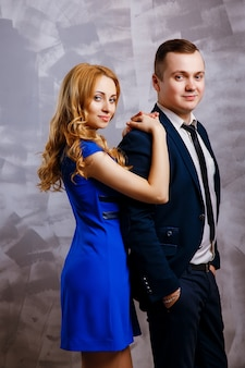 Handsome businessman in suit posing with beautiful blond woman in blue dress