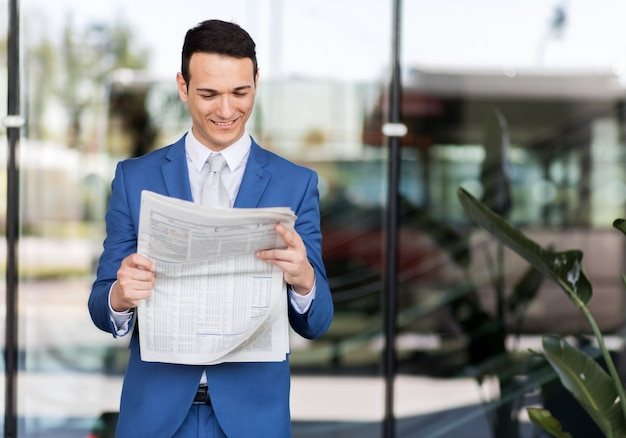 Handsome businessman in suit reading newspaper
