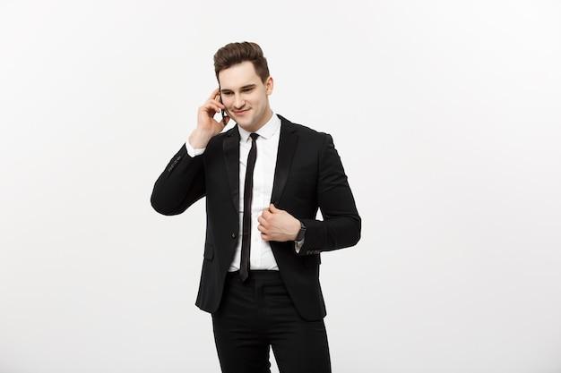 Uomo d'affari bello in vestito che parla sul telefono sopra fondo bianco isolato.