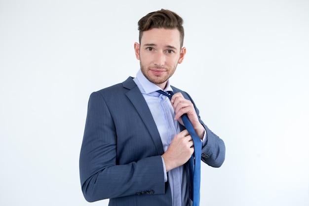 Uomo d'affari bello che toglie la cravatta