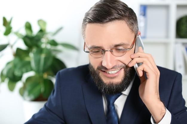 Красивый бизнесмен разговаривает по мобильному телефону в помещении