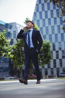 携帯電話で話しているハンサムな実業家