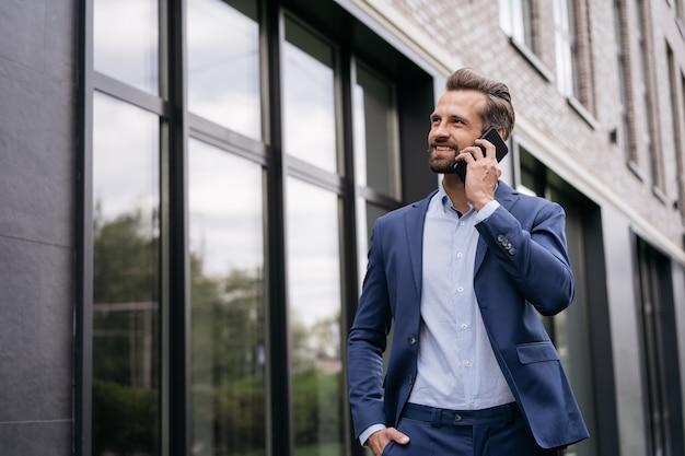 Красивый бизнесмен разговаривает по телефону