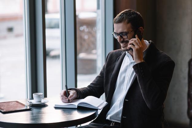 Красивый бизнесмен разговаривает по телефону в кафе