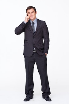 Handsome businessman talking on phone against white
