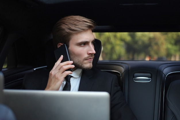Handsome businessman talking with phone sitting with laptop on the backseat of the car.