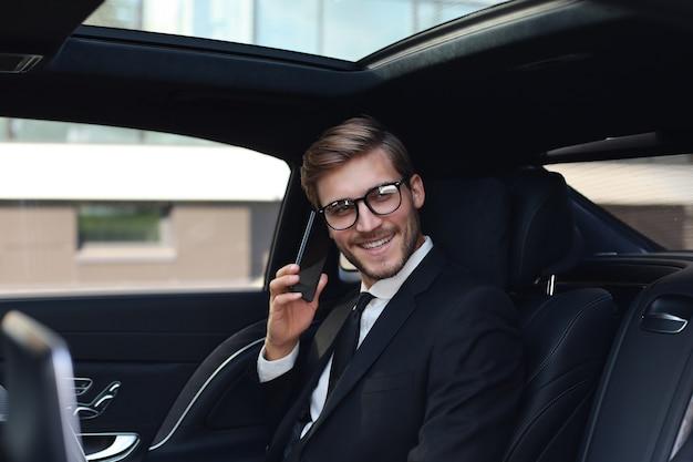 차 뒷좌석에 노트북과 함께 앉아 전화로 얘기하는 잘생긴 사업가.