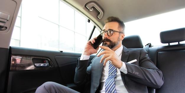Красивый бизнесмен разговаривает со смартфоном, сидя на заднем сиденье автомобиля