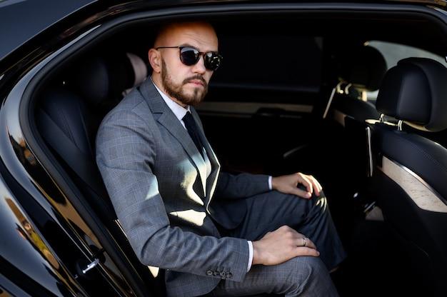 비즈니스 성공이라는 도시 개념의 중심에 운전사가 있는 현대 자동차에서 휴대전화를 사용하는 잘생긴 사업가