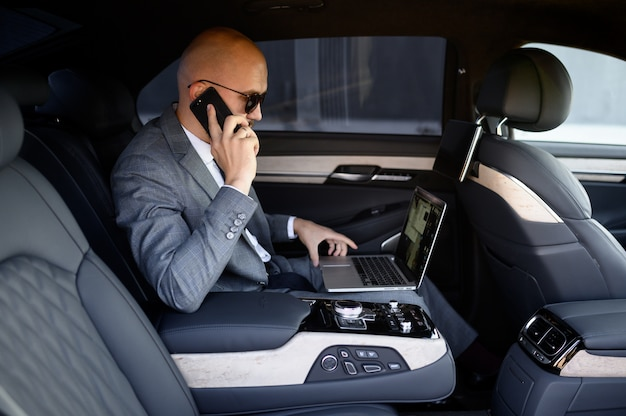 Handsome businessman using his mobile phone in a modern car with a driver in center of the city. concept of business