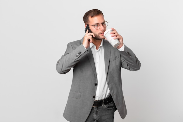 彼のスマートフォンを使用してハンサムなビジネスマン