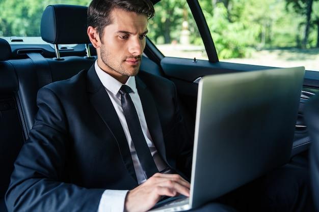 Handsome businessman using laptop in car