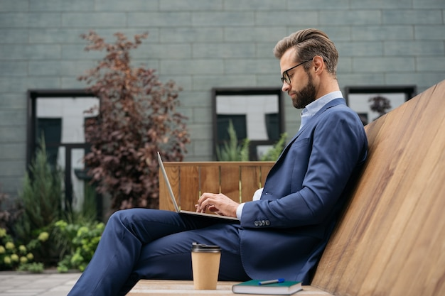 Handsome businessman using laptop computer searching online watching training courses