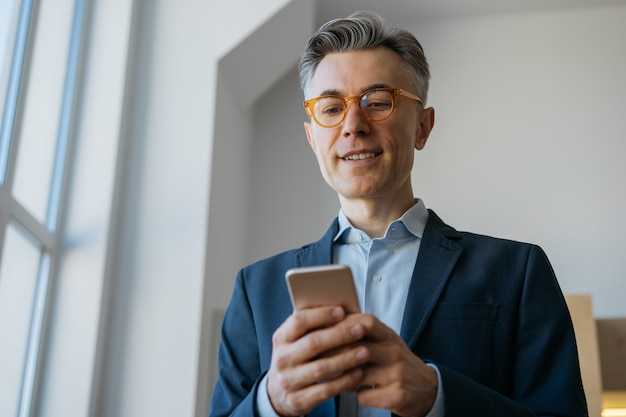 Handsome businessman using mobile phone app