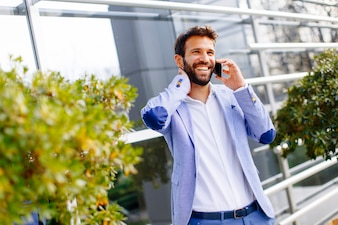 Handsome businessman using mobile phone in front of office building