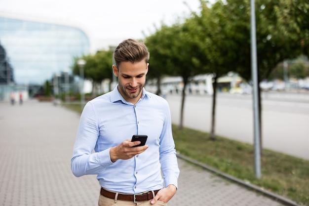 스마트폰을 사용 하 고 웃 고 잘생긴 사업가입니다. 휴대폰 앱을 사용하고, 문자 메시지를 보내고, 인터넷을 검색하고, 스마트폰을 보고 있는 행복한 청년. 모바일 기기로 작업하는 젊은이들.