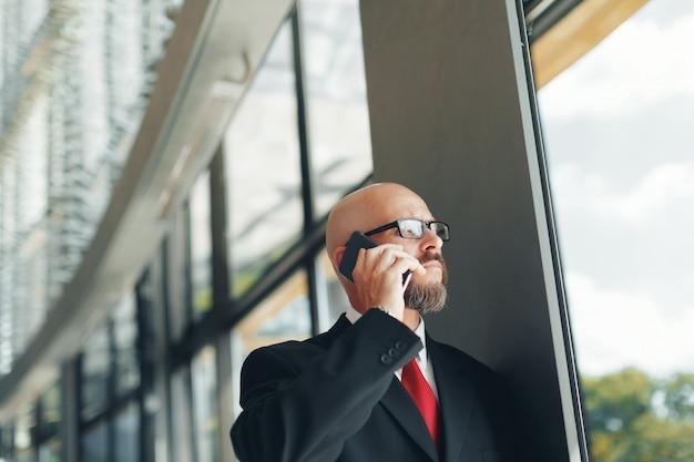 잘 생긴 사업가 사무실에서 스마트 폰을 사용하여