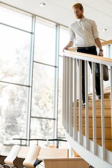 鞄を持って階段を降りるハンサムな実業家