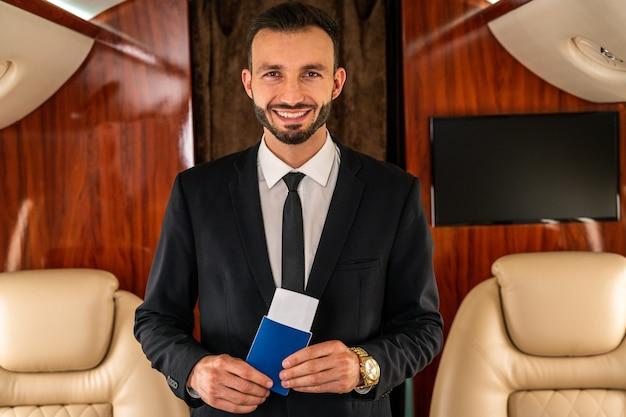 Красивый бизнесмен в элегантном костюме летит на эксклюзивном частном самолете