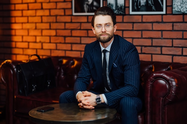 Handsome businessman wearing fashion eyeglasses and stylish suit sitting on the sofa at modern studio.
